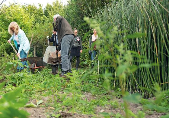Menschen arbeiten im Garten mit Schubkarre und Schaufel